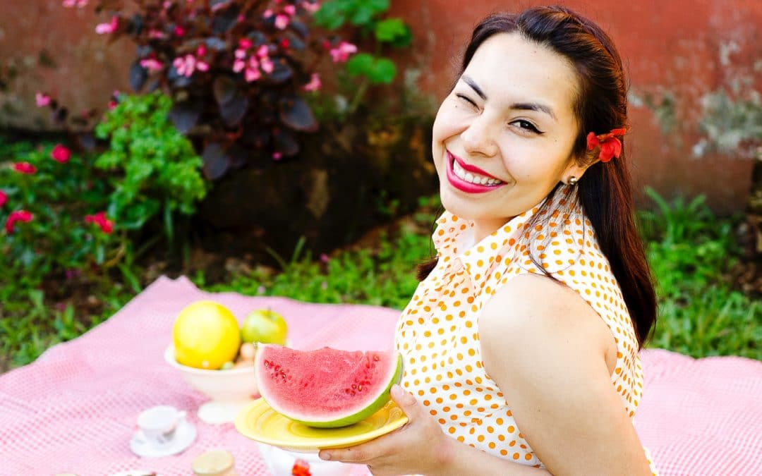 A woman on a picnic blanket holding up a watermelon slice and winking happily.